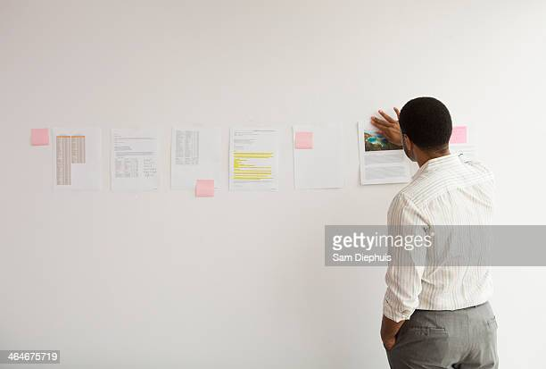 Black businessman taping up papers on office wall