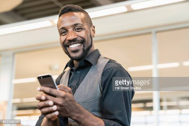 Black businessman texting with cell phone in office