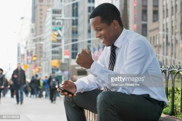 Black businessman texting with cell phone on city sidewalk