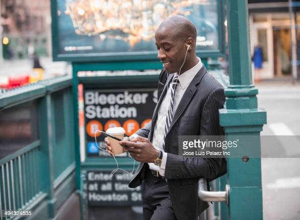 Black businessman using cell phone by subway entrance