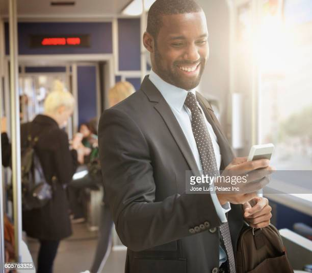 Black businessman using cell phone in subway