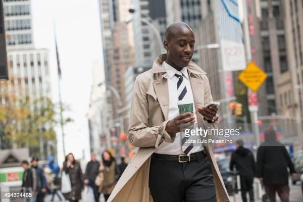 black businessman using cell phone on city street - トレンチコート ストックフォトと画像