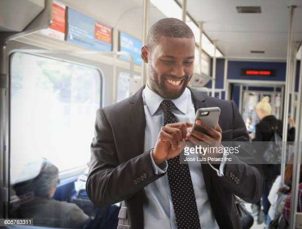 Black businessman using cell phone on subway