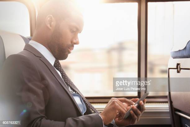 Black businessman using cell phone on subway