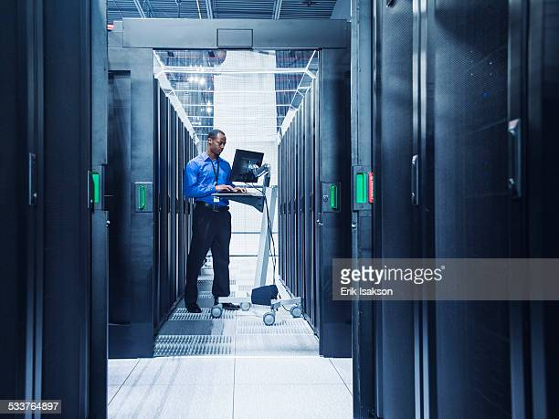 Black businessman using computer in server room