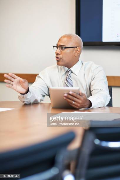 Black businessman using digital tablet in office meeting