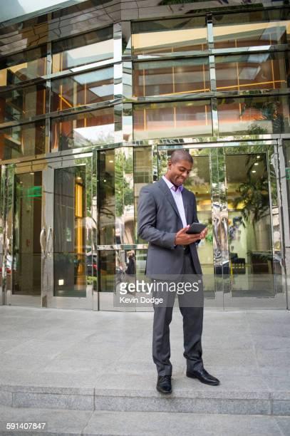 Black businessman using digital tablet outside office building