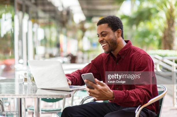 Black businessman using laptop and cell phone in cafe
