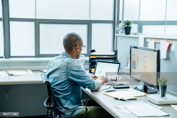 Black businessman using laptop in office