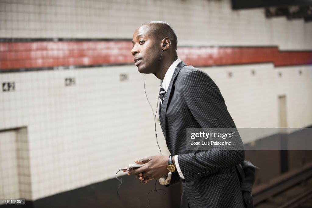 Black businessman waiting for subway on platform : Stock-Foto