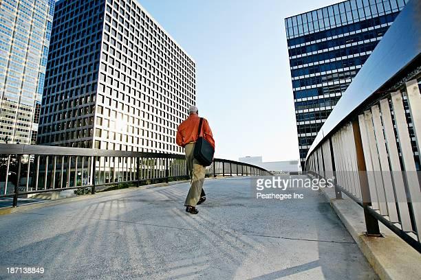 Black businessman walking on urban walkway