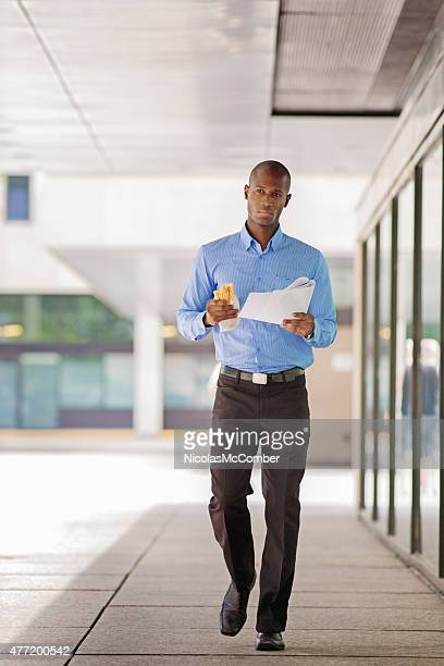 Black businessman walking with paper report and sandwich full length