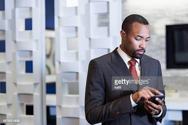 Homme d'affaires portant costume noir envoyer des SMS sur téléphone mobile