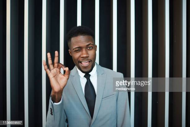 black businessman winking and gesturing ok - striped suit stock pictures, royalty-free photos & images