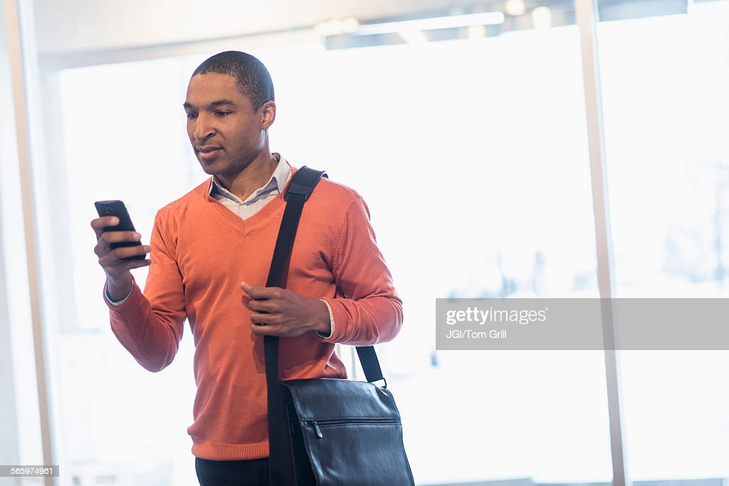 Black businessman with cell phone and messenger bag : Photo