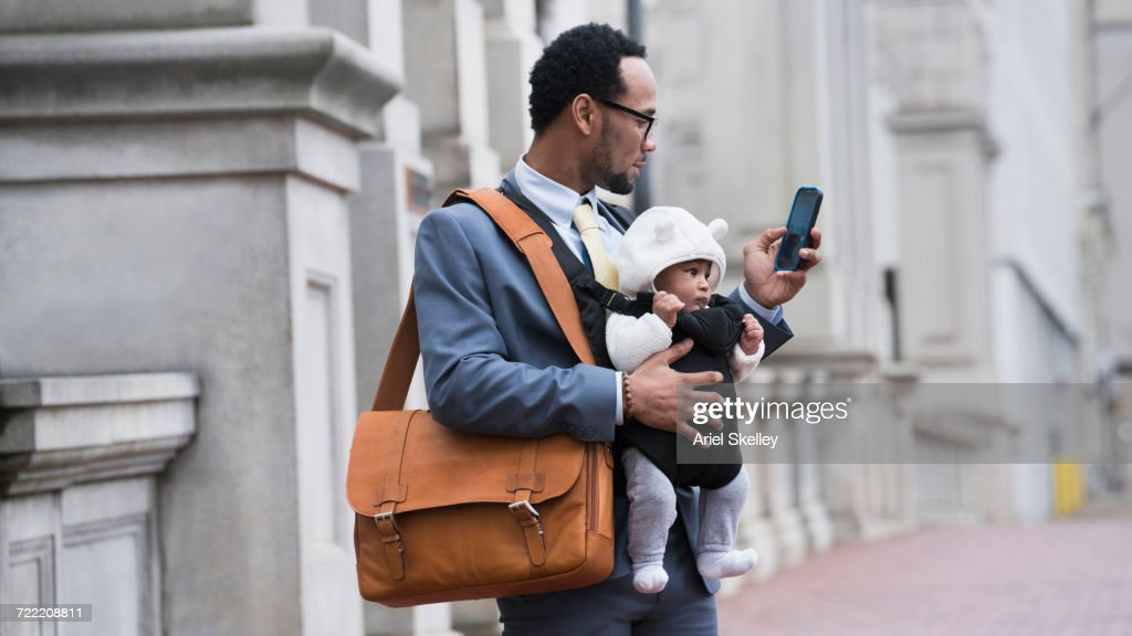 Black businessman with son in baby carrier texting on cell phone : Foto de stock
