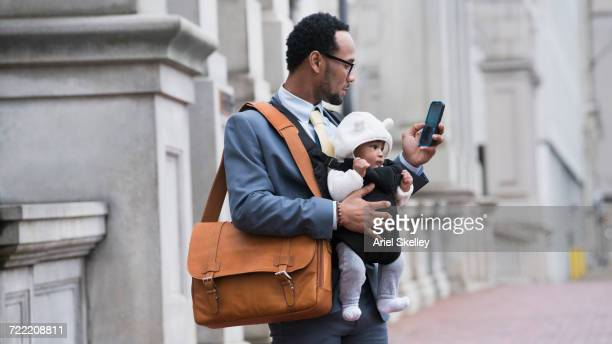 black businessman with son in baby carrier texting on cell phone - één ouder stockfoto's en -beelden