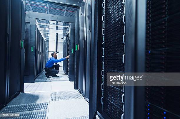 black businessman working in server room - network server stock pictures, royalty-free photos & images
