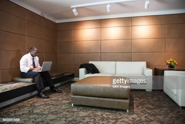 black businessman working on a lap top in a hotel lobby. - ottoman stock pictures, royalty-free photos & images