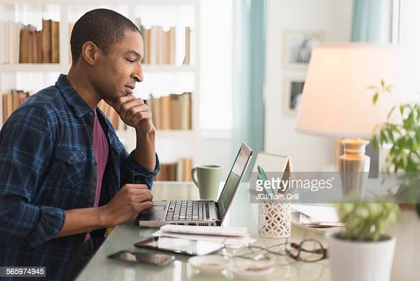 black businessman working on laptop at desk - one mid adult man only stock pictures, royalty-free photos & images