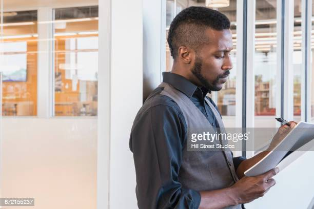 Black businessman writing in notebook in office