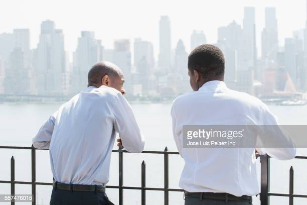 Black businessmen talking at city waterfront