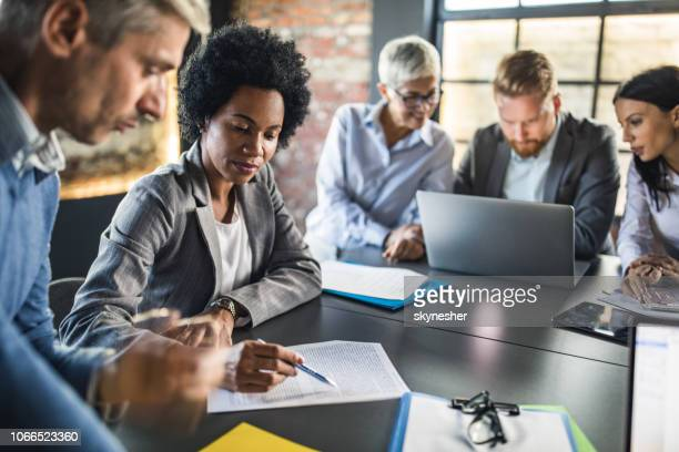 Black businesswoman and her colleague reading reports on a meeting in the office.