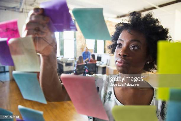 Black businesswoman arranging adhesive notes on glass wall