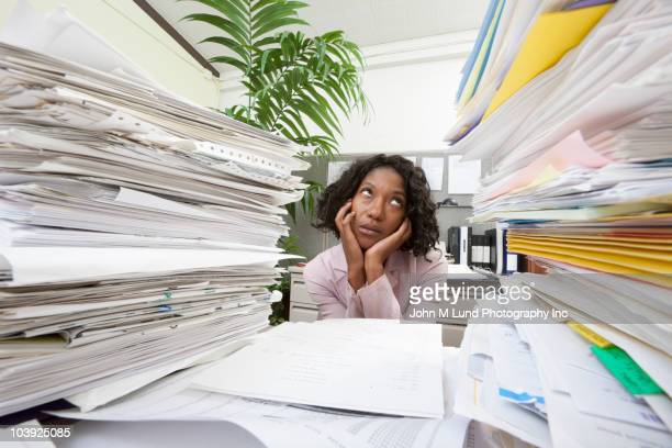 Black businesswoman between stacks of paperwork