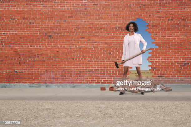 black businesswoman breaking through brick wall - superando as dificuldades - fotografias e filmes do acervo