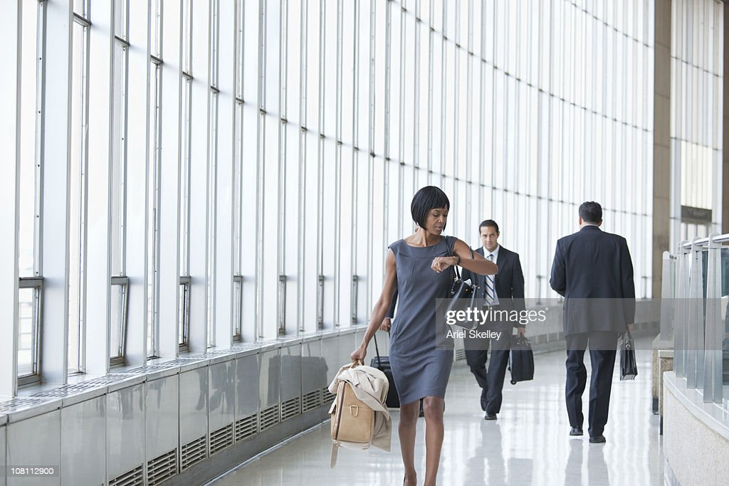 Black businesswoman checking the time on wristwatch in corridor : Foto de stock
