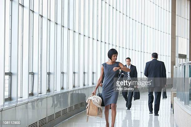 black businesswoman checking the time on wristwatch in corridor - ver a hora - fotografias e filmes do acervo