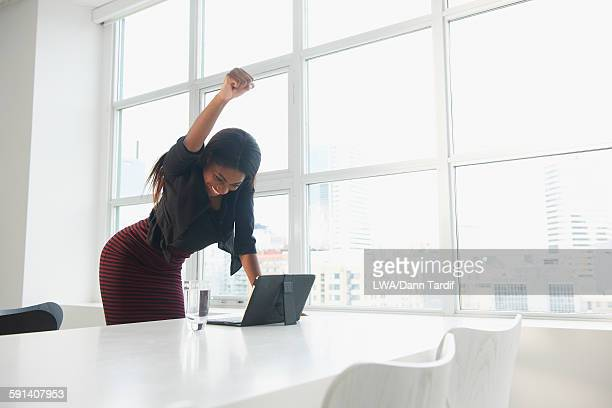 Black businesswoman cheering at digital tablet in office