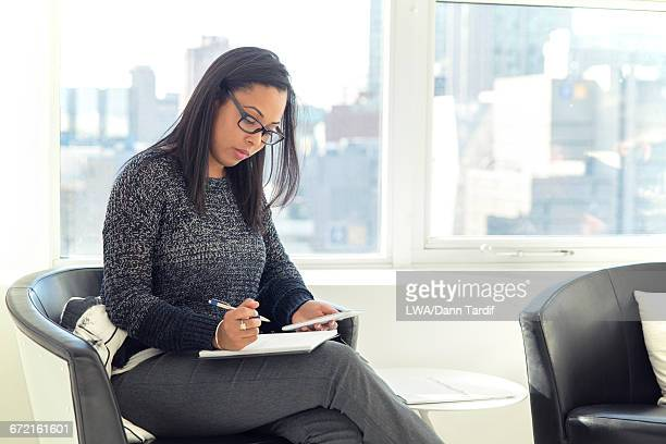 Black businesswoman holding cell phone writing in notebook