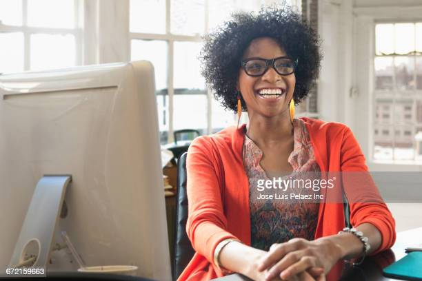 Black businesswoman laughing at desk