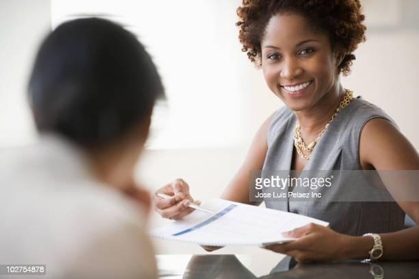 black businesswoman showing report to client - cliente - fotografias e filmes do acervo