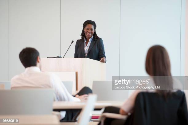 black businesswoman speaking at podium - presenter stock pictures, royalty-free photos & images