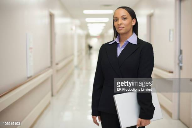 Black businesswoman standing in hospital hallway