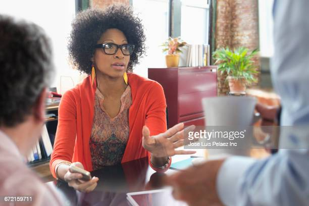 Black businesswoman talking in meeting at desk