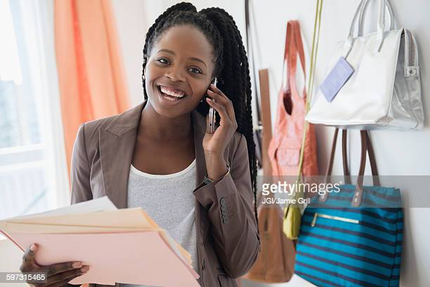 black businesswoman talking on cell phone - black purse stock photos and pictures