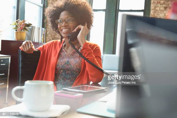 black businesswoman talking on telephone at desk - fastnät bildbanksfoton och bilder