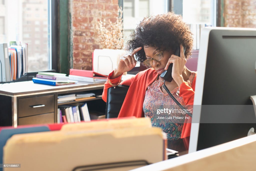 Black businesswoman talking on telephone at desk : Stock Photo