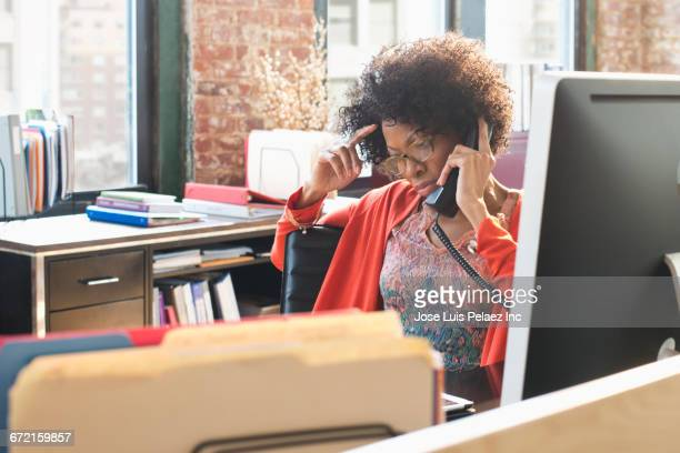 black businesswoman talking on telephone at desk - irritation stock pictures, royalty-free photos & images