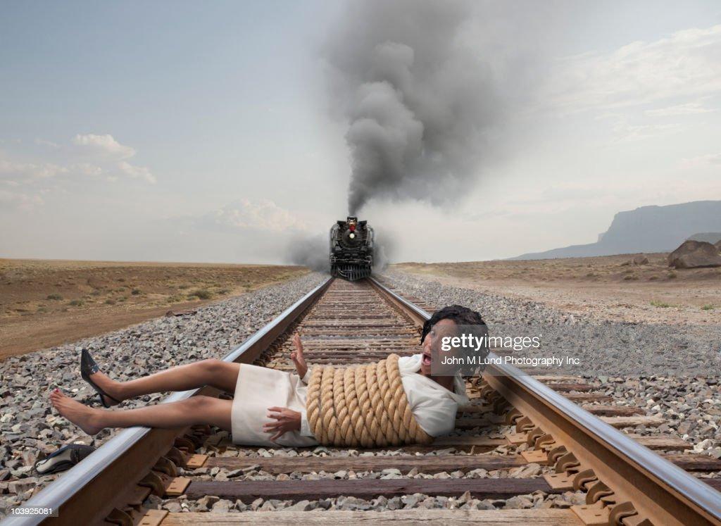 Black businesswoman tied to train tracks : Stock Photo