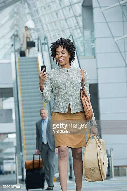 Black businesswoman using cell phone in lobby