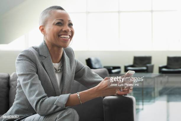 black businesswoman using cell phone on sofa in office - candid stock pictures, royalty-free photos & images