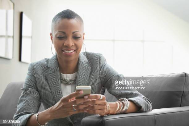 Black businesswoman using cell phone on sofa in office