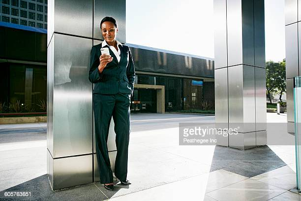 Black businesswoman using cell phone outdoors