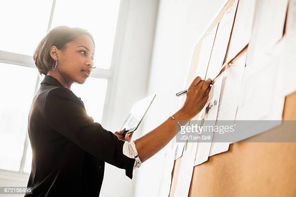 Black businesswoman using digital tablet writing on paperwork