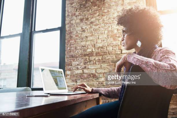 black businesswoman using laptop at desk - convenience stock pictures, royalty-free photos & images